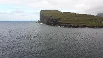 Image: View across the sound to the northwestern tip of Eysturoy and the village Eiði. Also seen are the basalt columns of Risin and Kellingin.
