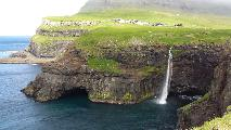 Image: The village of Gásadalur and the famous waterfall. Notice the grazing sheep on the cliffs.